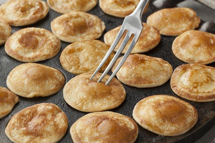 Baking Dutch mini pancakes called poffertjes
