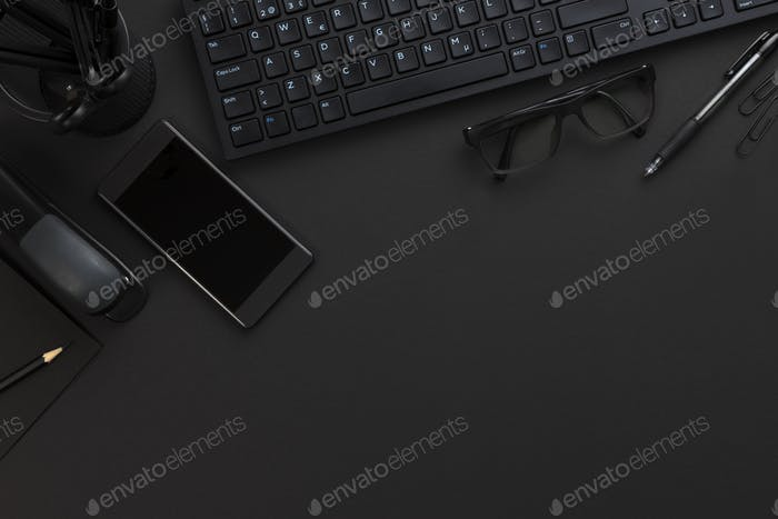 Top view of pitch black office desk with computer and supplies