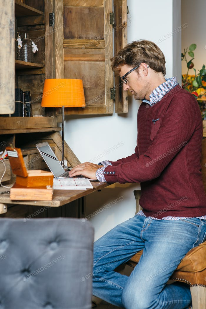 Young man in glasses working on laptop