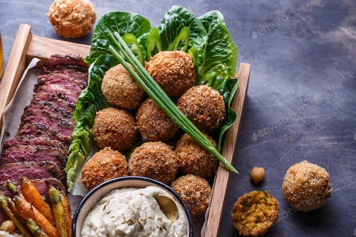 Schließen Blick auf Falafel, Babaghanoush und Pastrami in der Holzkiste, Copyspace.