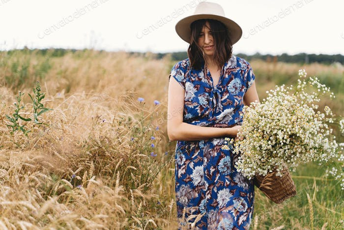 Stylish young woman in blue vintage dress and hat gathering white wildflowers