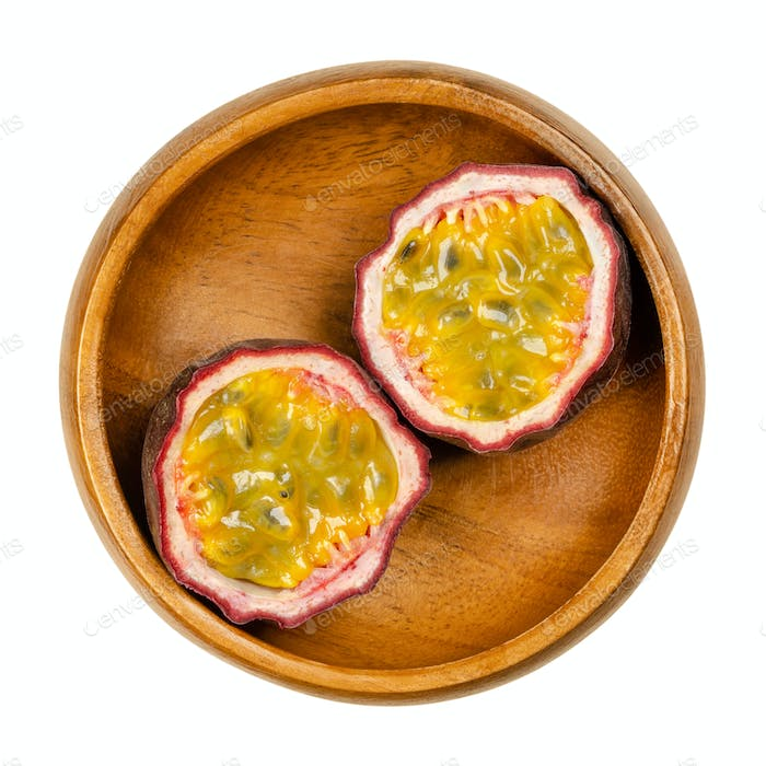 Fresh passion fruit cut in two halves, in a wooden bowl