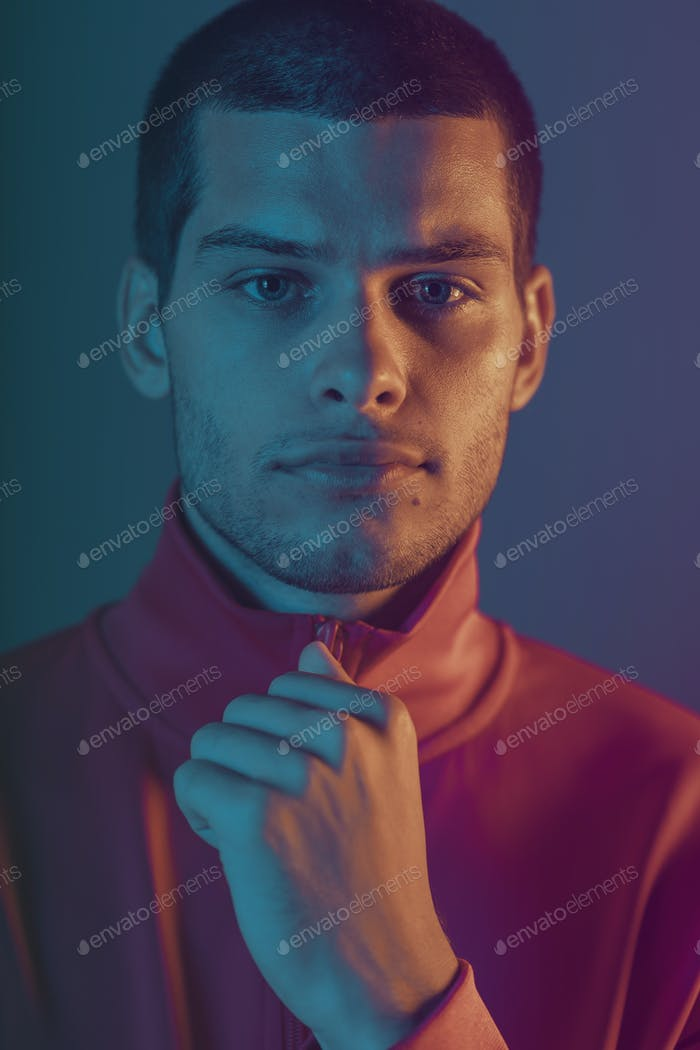 Studio close-up portrait of attractive male model. Color flash studio light