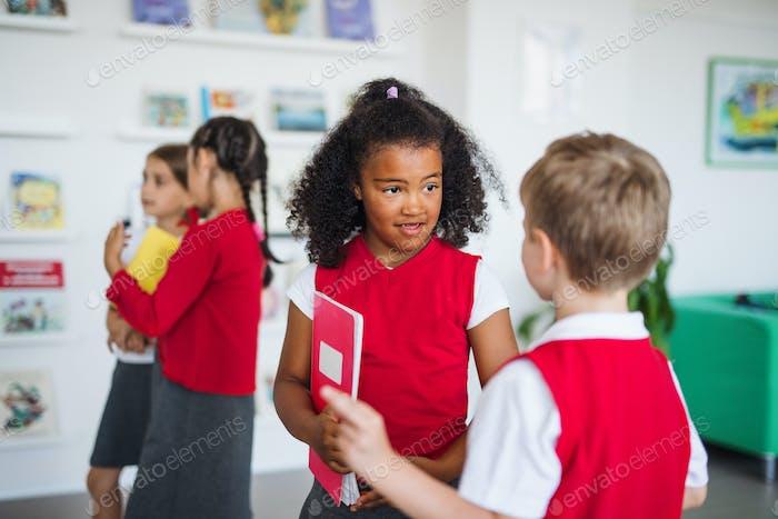 Eine Gruppe von fröhlichen kleinen Schulkindern im Flur, stehend und reden