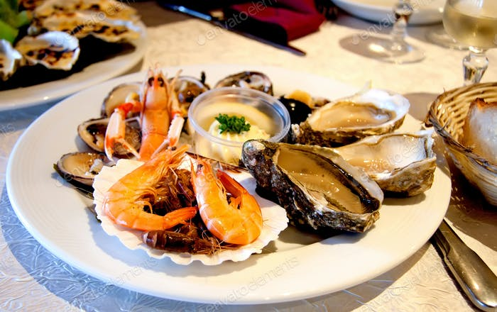 Fresh seafood platter with lobster, shrimps and oysters on the table