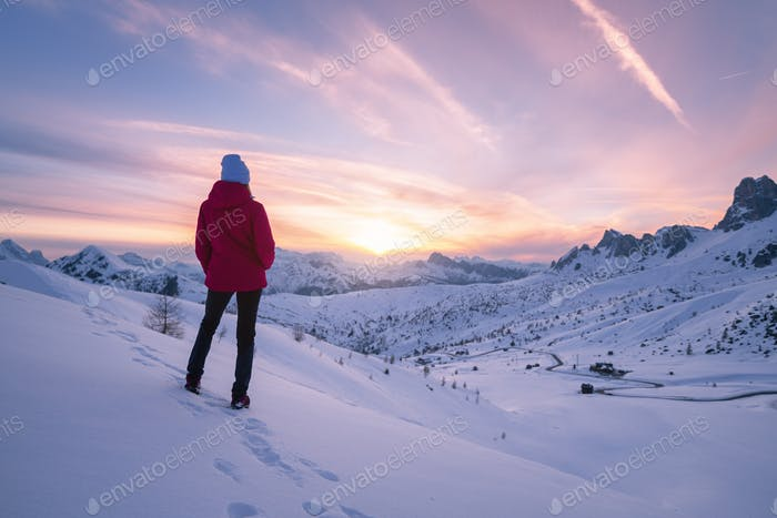 Young woman in snowy mountains at sunset in winter