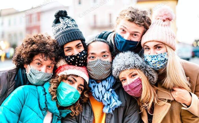 Multiracial friends taking selfie wearing face mask and winter clothes