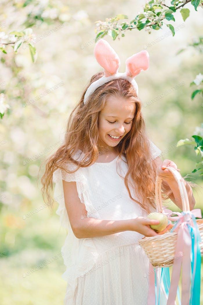 Entzückendes kleines Mädchen im blühenden Apfelgarten am schönen Frühlingstag