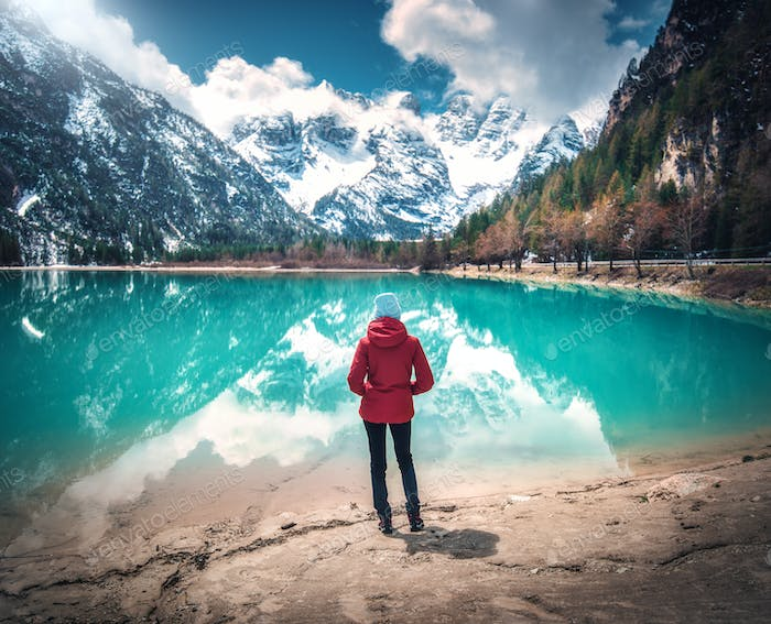 Young woman in red jacket is standing near lake with azure water
