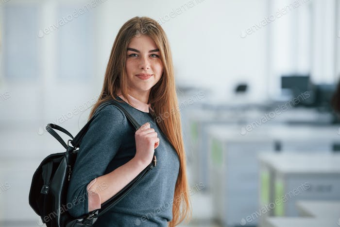 Cute freckles. Portrait of attractive young woman standing in the office with black bag
