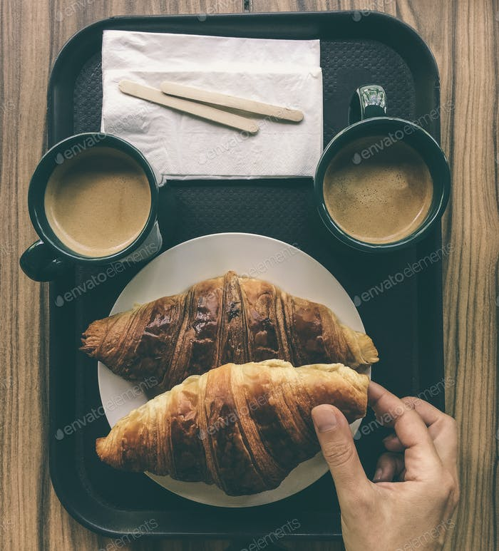 Croissant and  coffee breakfast.