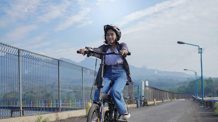 Joven asiática andar en bicicleta para trabajar ella es feliz y segura