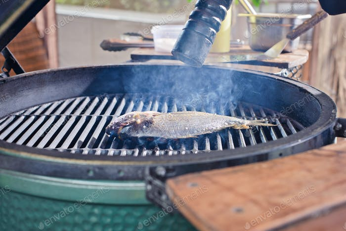 the process of making fresh raw fish dorado hands chef puts fish on the grill roaster