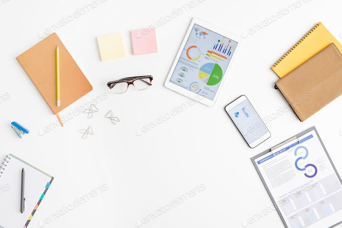 Top view of supplies of office worker including financial papers in clipboard