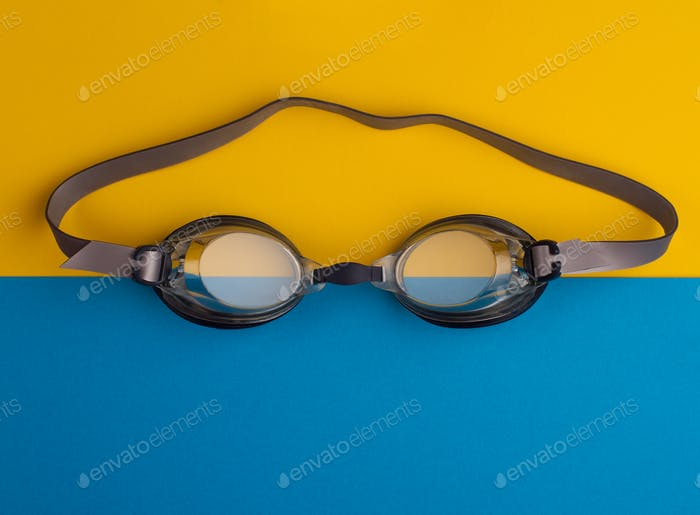swimming goggles on blue and yellow background