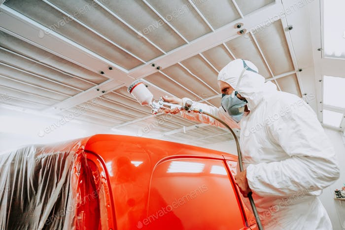 Auto mechanic painting with spray gun car in special booth