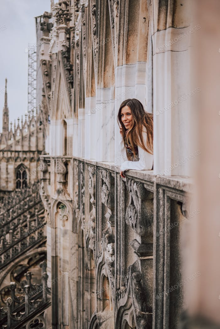 Young woman contemplating the city from Milan Cathedral