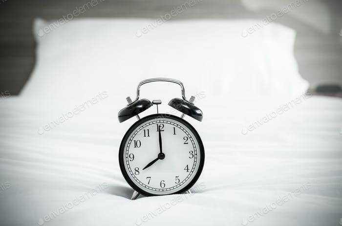 Vintage alarm clock on the bed