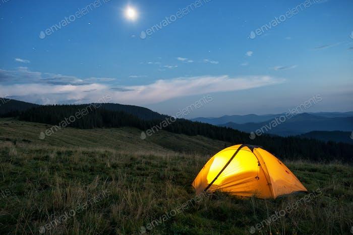Beleuchtetes orangefarbenes Zelt in den Bergen bei Dämmerung