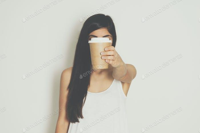 Mujer sosteniendo taza de Papel marrón de café caliente.