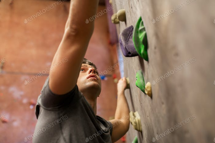 young man exercising at indoor climbing gym