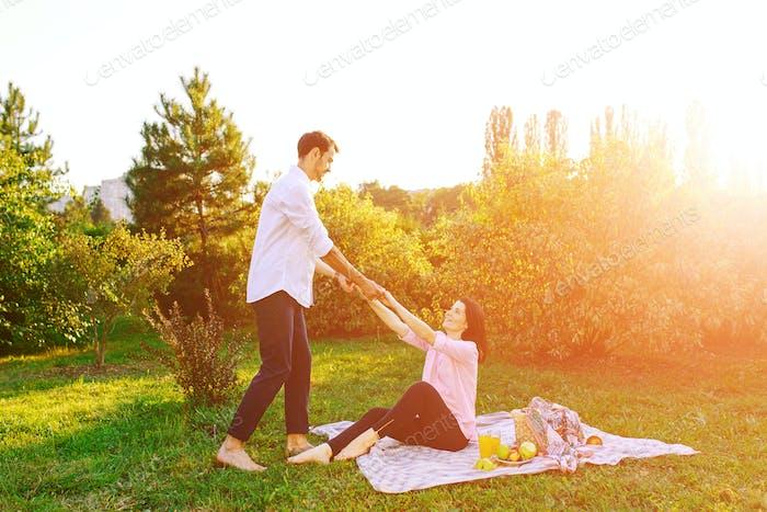 Happy pregnant couple in park on picnik