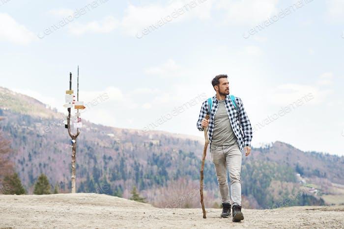 Mann mit Rucksack und Stock genießen die Aussicht in die Berge