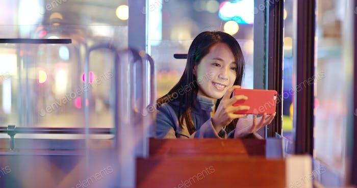 Frau nehmen Foto auf der Straßenbahn in der Nacht