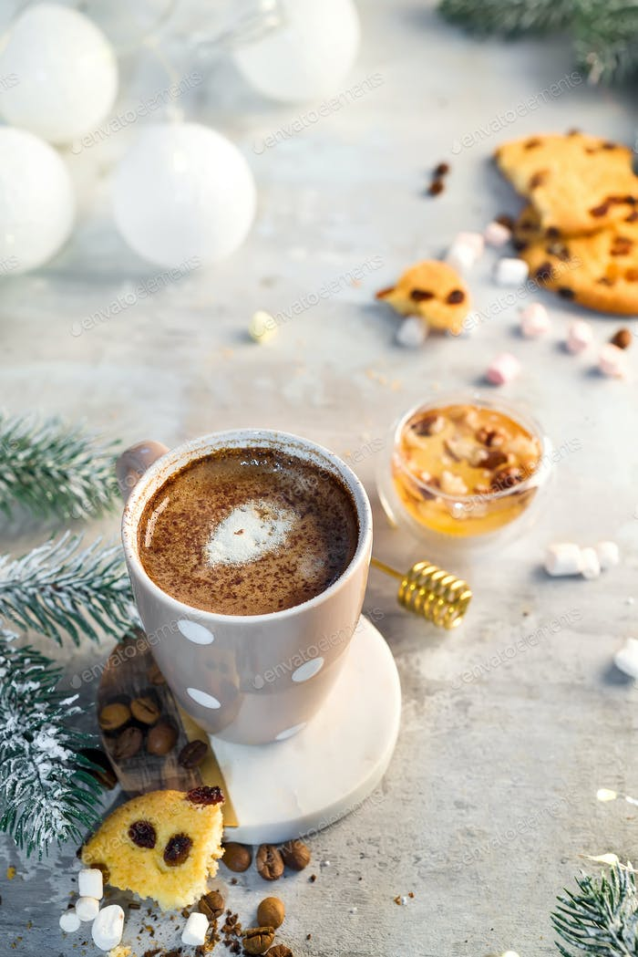 Hot cappuccino with marshmallows in a ceramic cup with honey and metal honey stick on a wooden dark