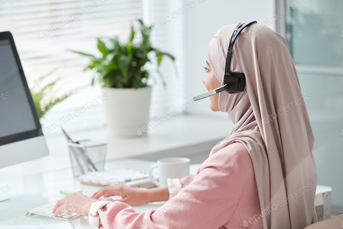 Contemporary young Muslim female operator in hijab and headset typing in office