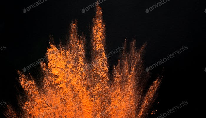 Abstract colored dust explosion of orange holi on black