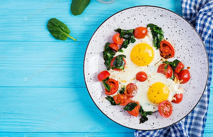 Breakfast. Ketogenic diet food. Fried egg, spinach, and tomatoes.