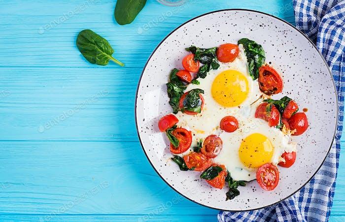 Frühstück. Ketogene Diätkost. Spiegelei, Spinat und Tomaten.