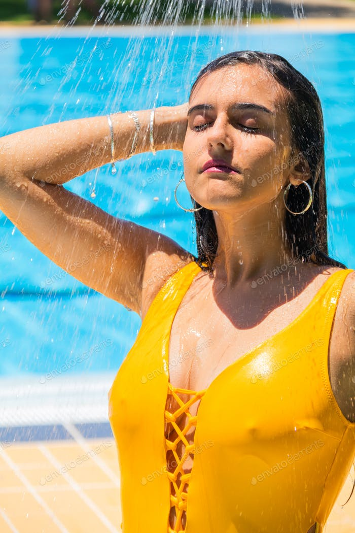 Young girl wear bikini standing under the outdoor pool shower.