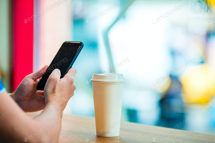 Closeup of male hands holding cellphone and glass of coffee in cafe