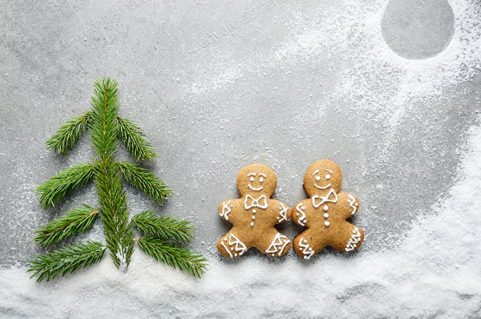 Flat lay of two gingerbread men having a walk on snow near fir t