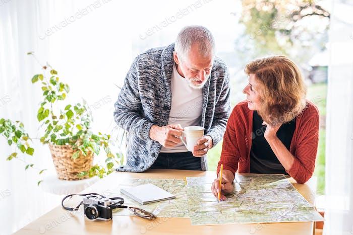 Älteres Paar mit Karte zu Hause, Pläne zu machen.