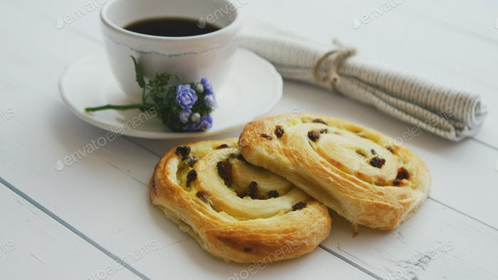 Delicious pastry with raisins and a cup of coffee top view