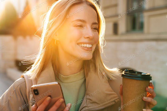 Portrait of woman using cellphone and drinking coffee while walking
