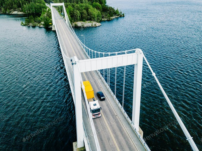 Aerial view of white suspension bridge with car crossing over blue lake in Finland