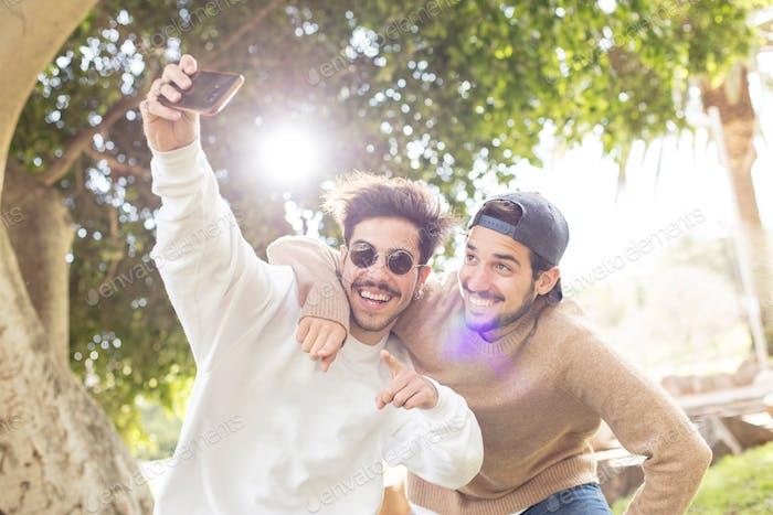 Men taking selfie in park