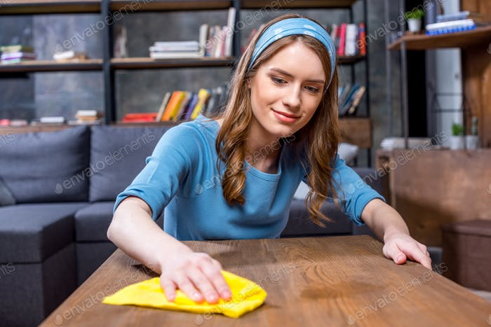 Young smiling woman wiping table with yellow rag