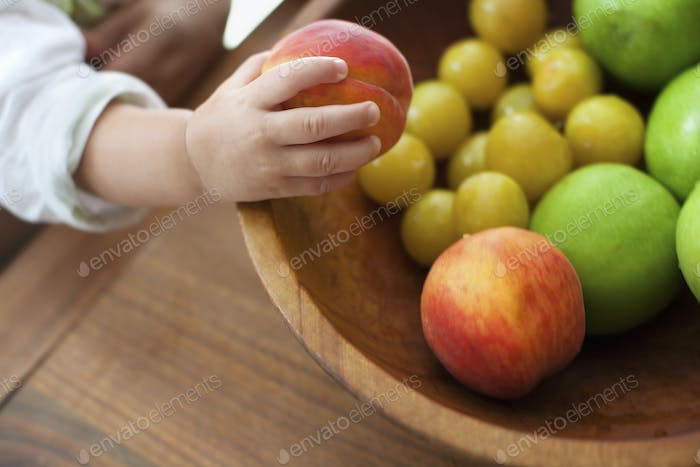 A small child, a one year old girl, grasping fruit from a bowl.