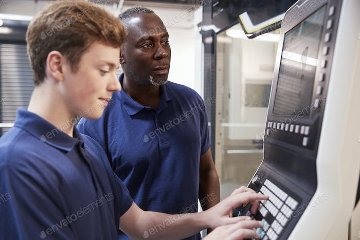Engineer Showing Apprentice How To Use CNC Tool Making Machine