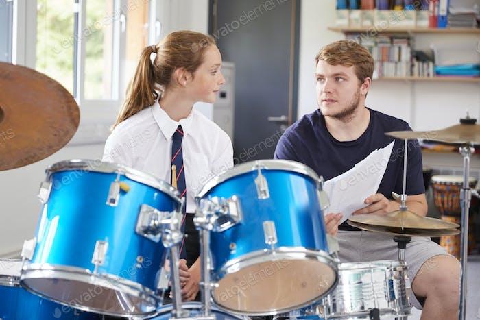 Weibliche Schüler mit Lehrer spielen Trommeln in Musik Lektion