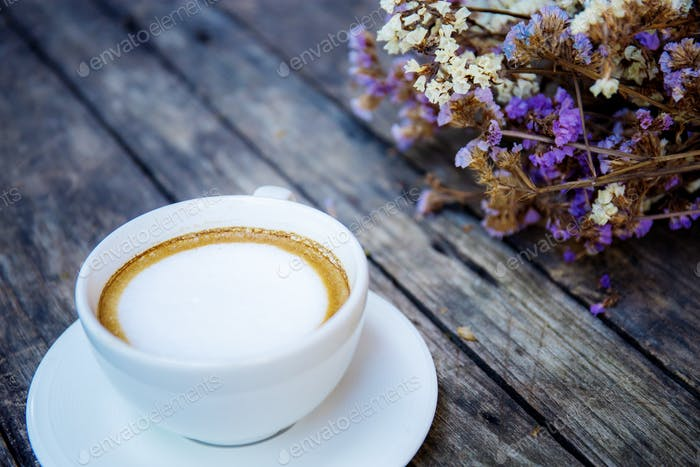 Coofee cup and flower on wood