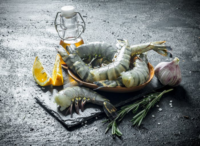 Whole shrimps raw on a stone Board with slices of lemon.