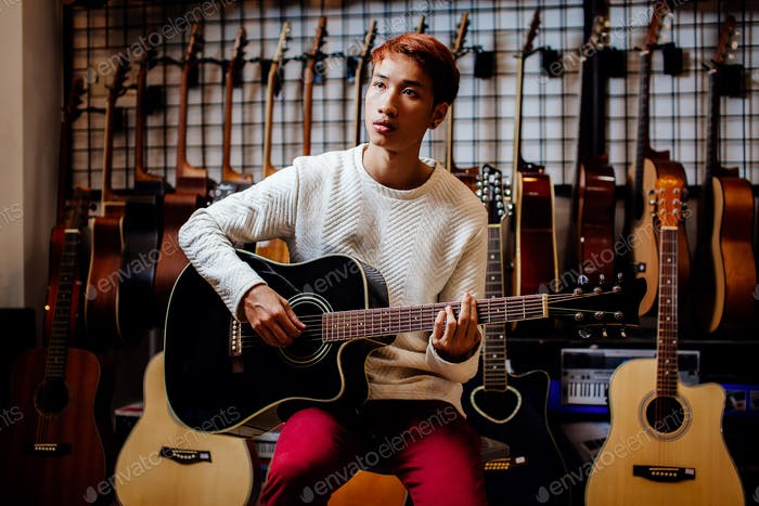 handsome asian teenage man playing guitar in guitar shop