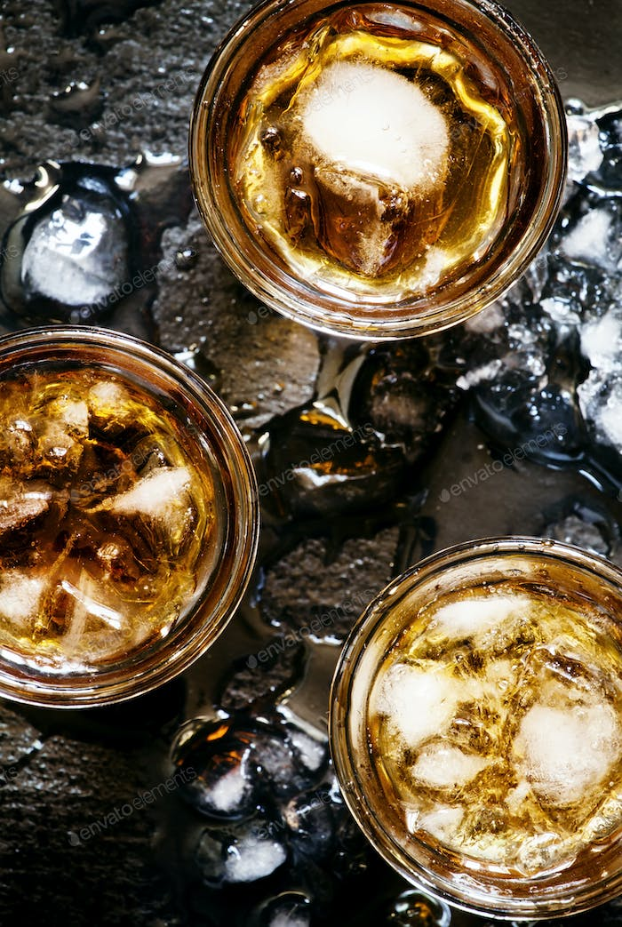 Cold whiskey in a glass with crushed ice on a black stone wet background, top view