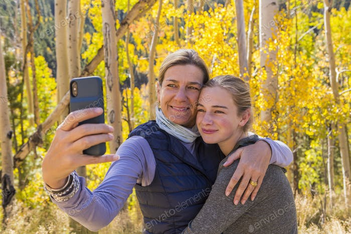retrato de la madre y su hija de 13 años con aspens otoño en el fondo, tomando un selfie